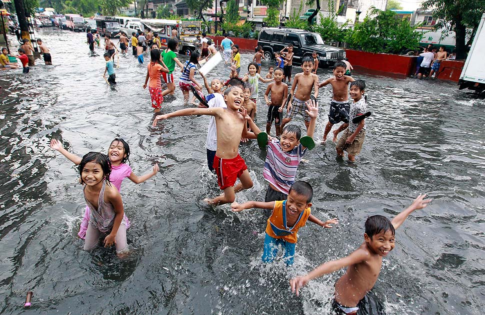 Filipino children play in  a flooded street